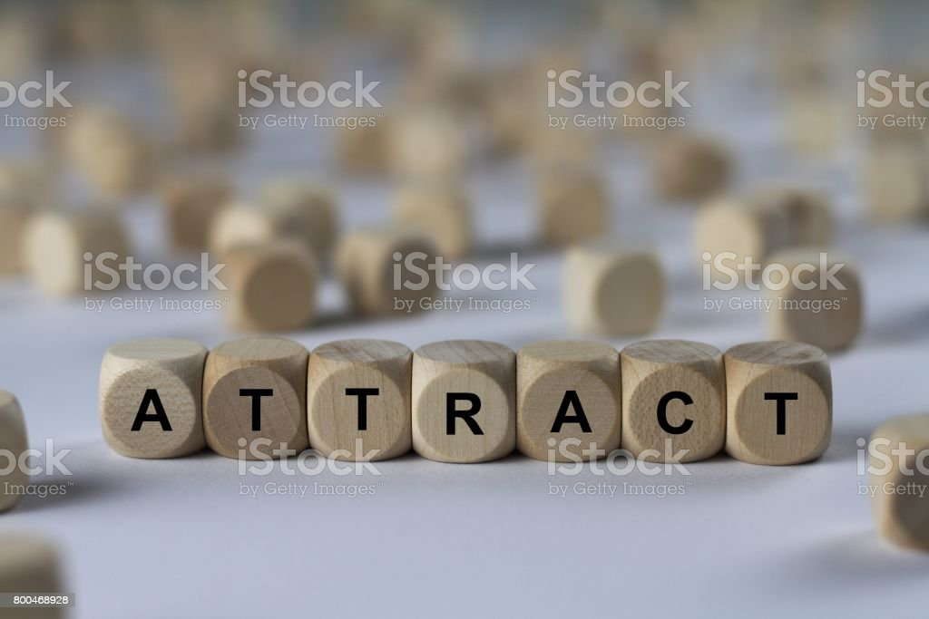 attract - cube with letters, sign with wooden cubes stock photo