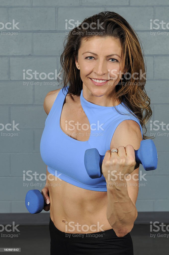 Attractive 30ish Woman Using Weights In Gym royalty-free stock photo