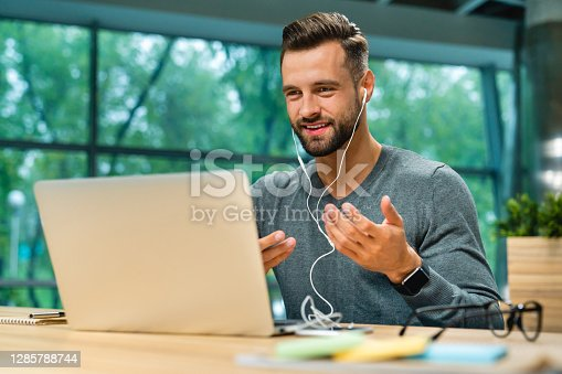 Attractive 30s caucasian businessman having online conversation using laptop and headphones at office desk