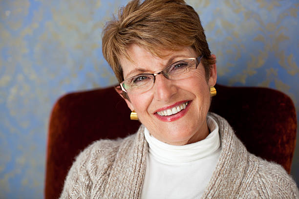 attractive 60 year old woman smiling at the camera stock photo