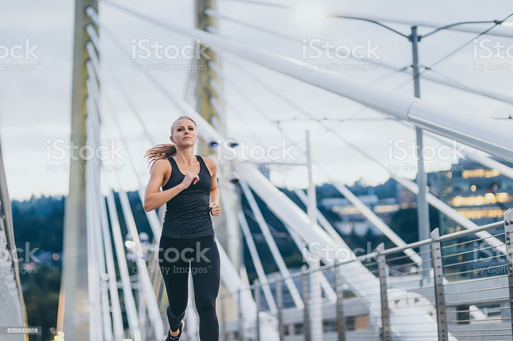 Attractive adult female running over a bridge at dusk stock photo