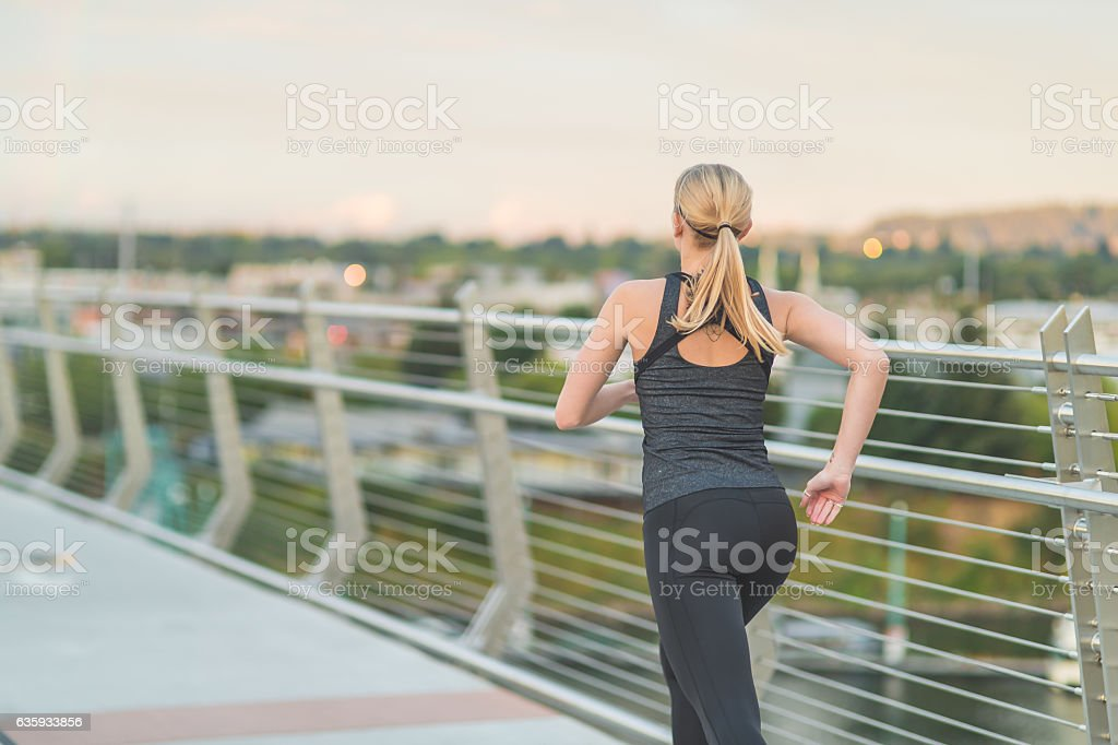 Attractive adult female running over a bridge stock photo