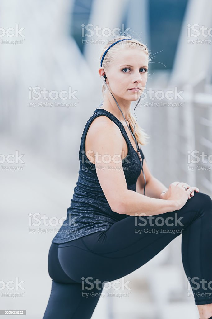 Attractive adult female stretching before a chilly run during fall stock photo