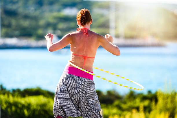 attraktive erwachsene frau spielt mit hula-hoop in der natur. - hula hoop workout stock-fotos und bilder