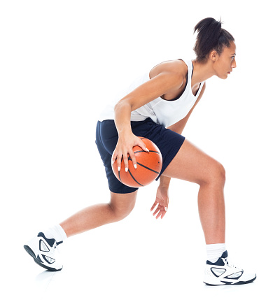 Attractive African American female playing basketball