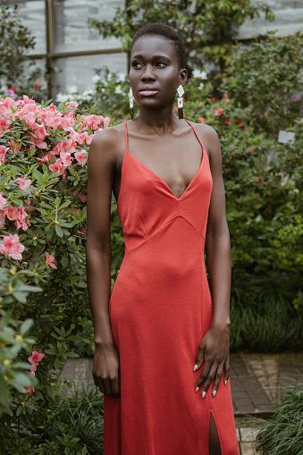 Chica Atractiva Afroamericana Con El Pelo Corto En Vestido Rojo Posando En El Jardín Con Flores Foto de stock y más banco de imágenes de A la moda