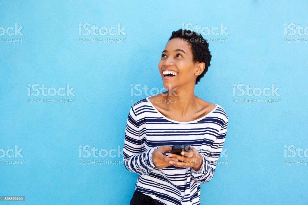 jolie femme afro-américaine, tenant le téléphone portable par mur bleu - Photo