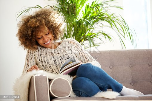 Portrait of attractive african american woman sitting on sofa reading book