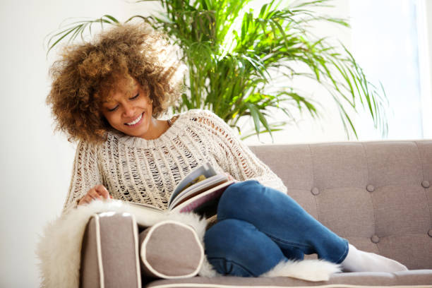 attractive african american woman sitting on sofa reading book - reading стоковые фото и изображения