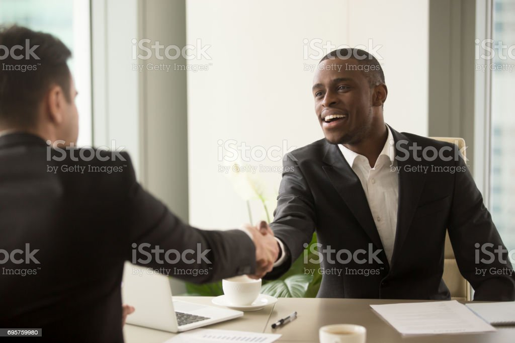 Attractive african businessman and caucasian business partner handshaking, multi-ethnic partnership stock photo