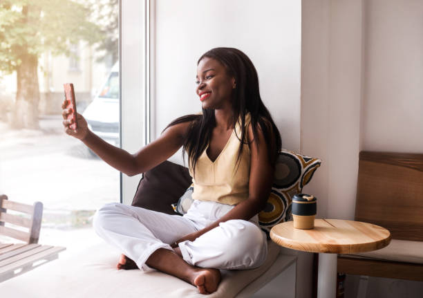 attractive african girl makes selfie at the windowsill at cafe. - video call foto e immagini stock