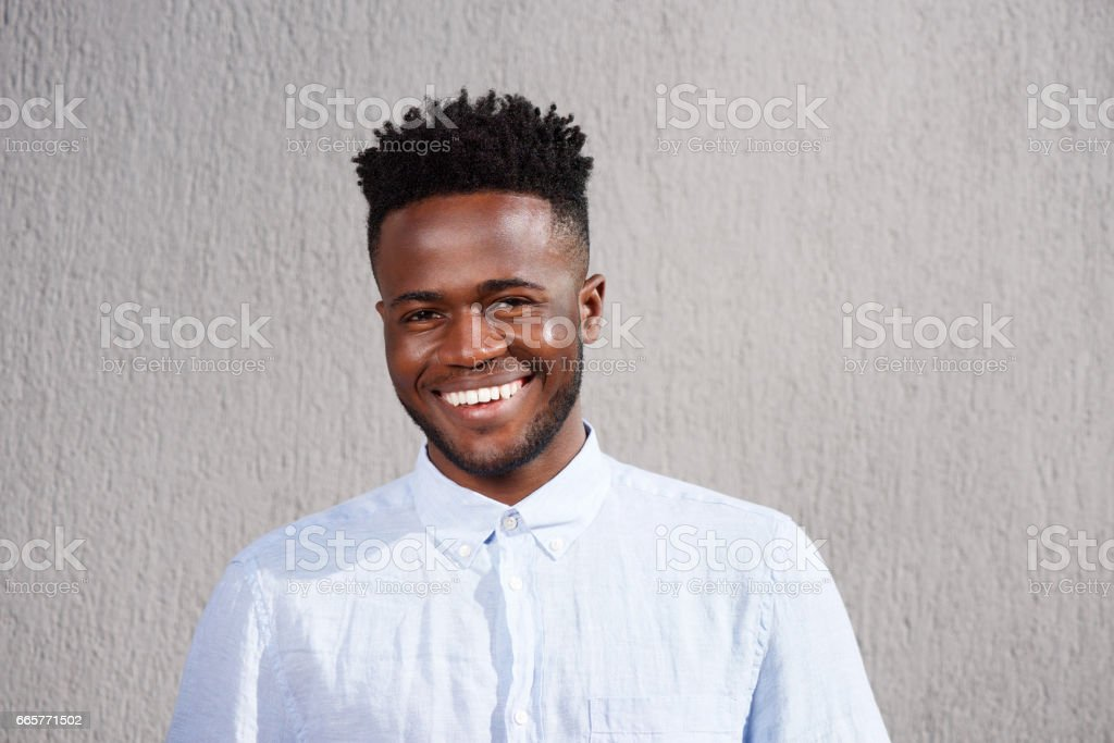 attractive African man smiling and standing by wall stock photo