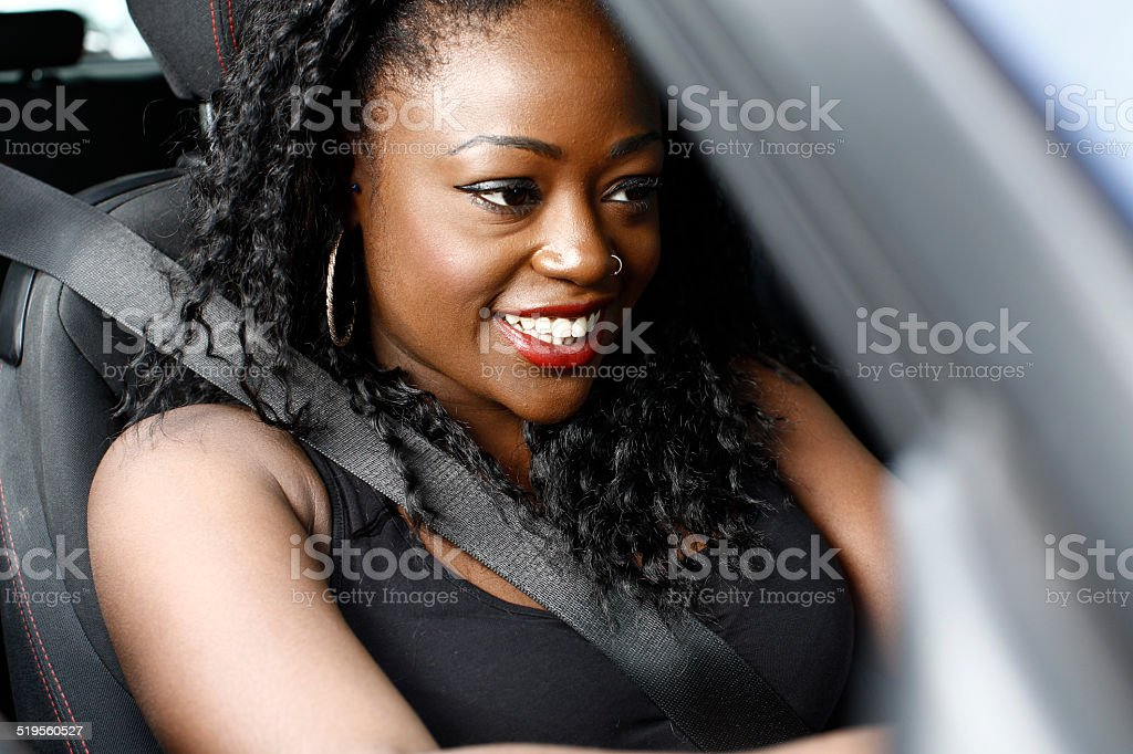 Attractive African woman driving her car stock photo