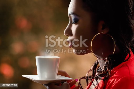Close up side view of attractive african woman smelling scent of hot beverage.Low key portrait of woman with directional backlit ambient light holding cup with coffee.