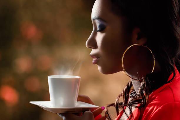 attractive african woman smelling hot cup of coffee. - annusare foto e immagini stock