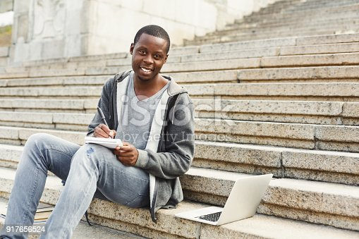istock Attractive african-american student making notes sitting on stairs outdoors 917656524