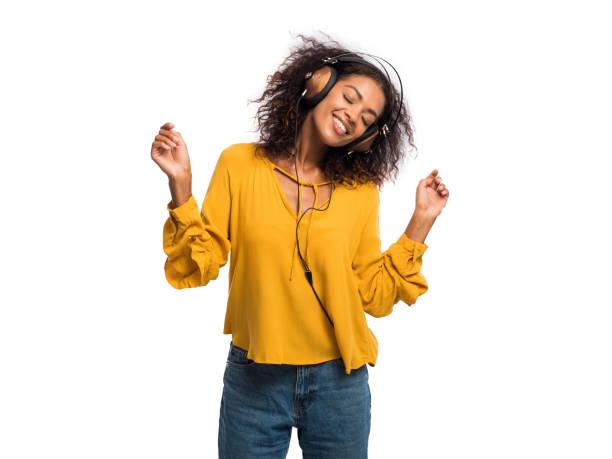 有吸引力的非洲裔美國年輕婦女聽音樂與耳機和舞蹈在白色牆壁背景。女孩在黃色秋天頂部。工作室拍攝。音樂理念 - music 個照片及圖片檔