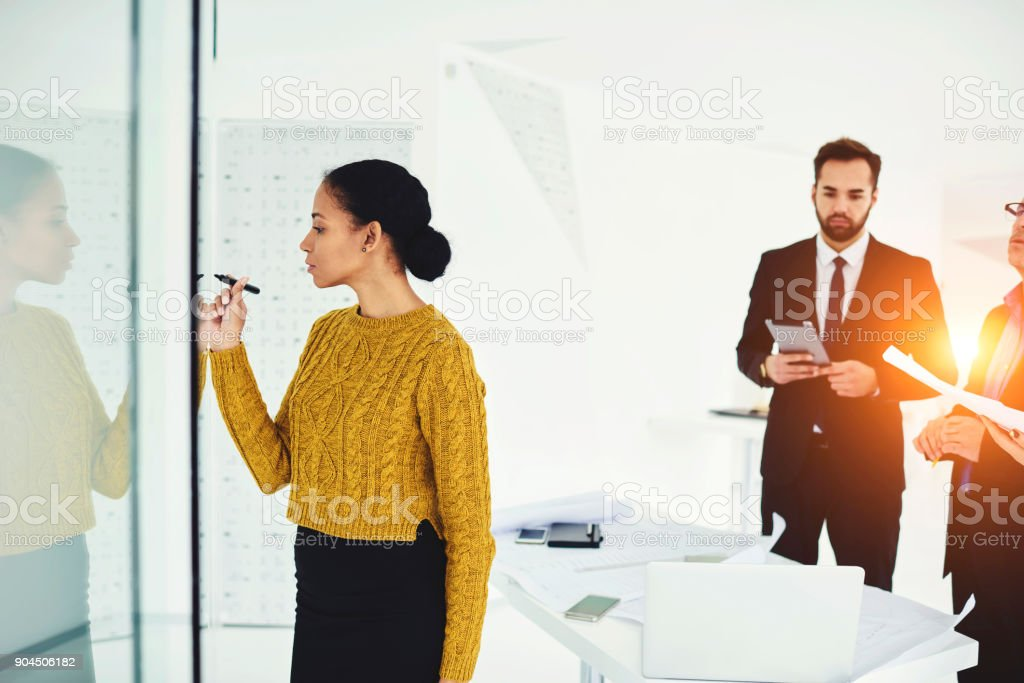 Attractive afro american female secretary assistant writing on board plan of conference meeting include important themes must be discussed during formal meeting with professional traders partners stock photo