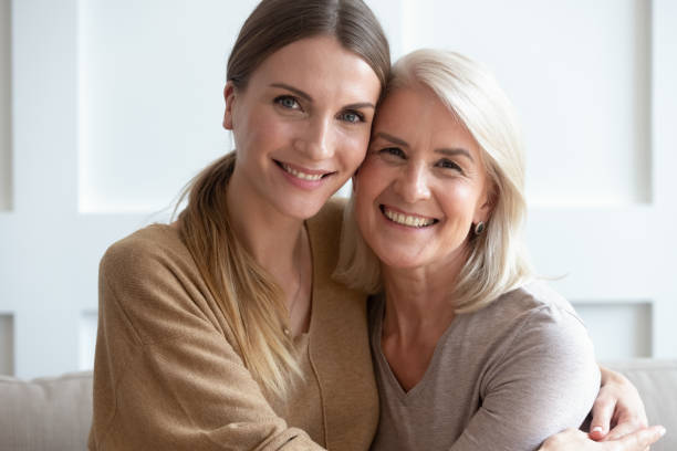 atractiva madre y niña adulta abrazando mirando a la cámara - hija fotografías e imágenes de stock