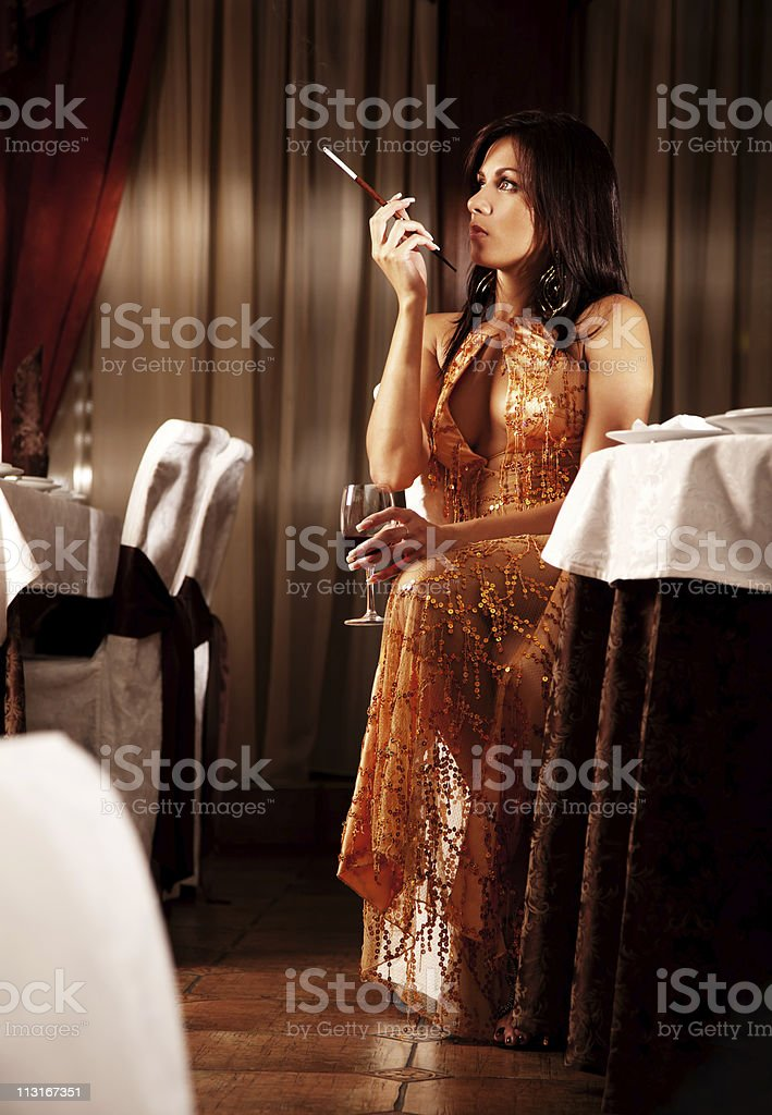 Attractive alone woman smoking cigarette at restaurant royalty-free stock photo