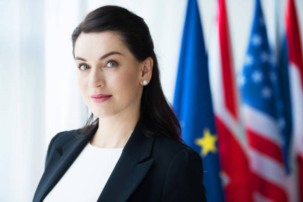 attractive ambassador looking at camera near flags attractive ambassador looking at camera near flags diplomacy stock pictures, royalty-free photos & images