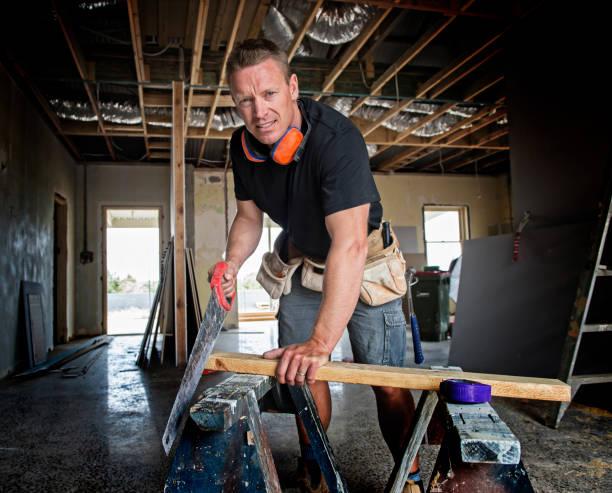 attraktive und selbstbewusste Konstruktor Zimmermann oder Baumeister Mann Schneiden von Holz mit manueller Arbeit sah auf industrielle Baustelle in Installation und Renovierung blauen Kragen Arbeit Industrie – Foto
