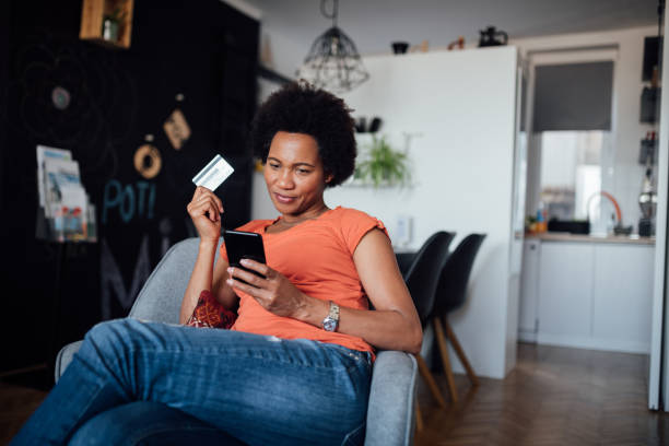 Attractive and happy African American woman shopping online stock photo