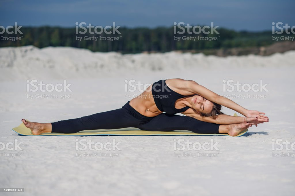 Attractive and healthy young woman doing exercises on the beach at sunrise or sunset. stock photo