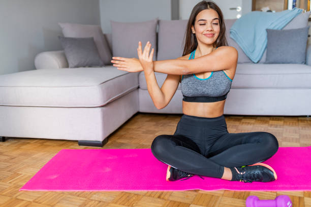 attractive and healthy young woman doing exercises while resting at home - peso mosca foto e immagini stock