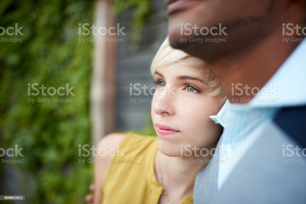 Attractive and stylish multicultural couple in love cuddling by a fence in an ivy-filled urban setting stock photo