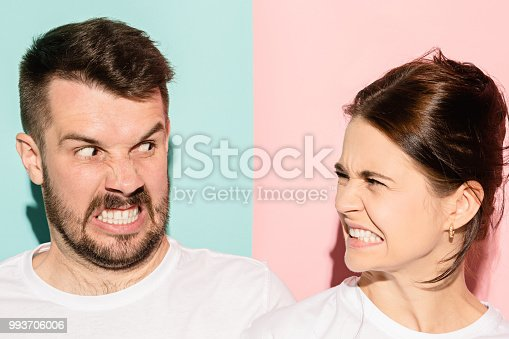993706062 istock photo attractive angry couple fighting and shouting at each other 993706006