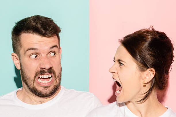 attractive angry couple fighting and shouting at each other The attractive angry couple fighting and shouting at each other. quarrel concept. The studio shot on trendy pink and blue background. Human emotions concept confrontation stock pictures, royalty-free photos & images