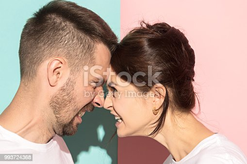 993706062 istock photo attractive angry couple fighting and shouting at each other 993724368