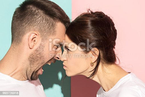 993706062 istock photo attractive angry couple fighting and shouting at each other 993726918
