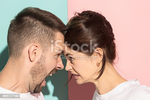 993706062 istock photo attractive angry couple fighting and shouting at each other 993727160