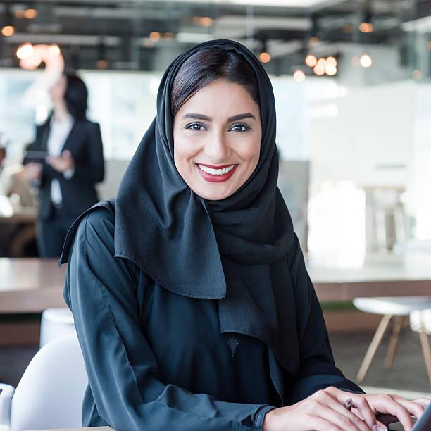 attractive arab businesswoman wearing hijab smiling towards camera - emirati woman 個照片及圖片檔