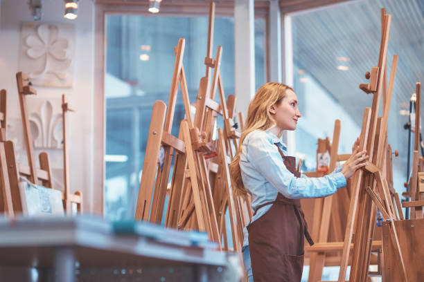 Attractive artist painting at the easel stock photo