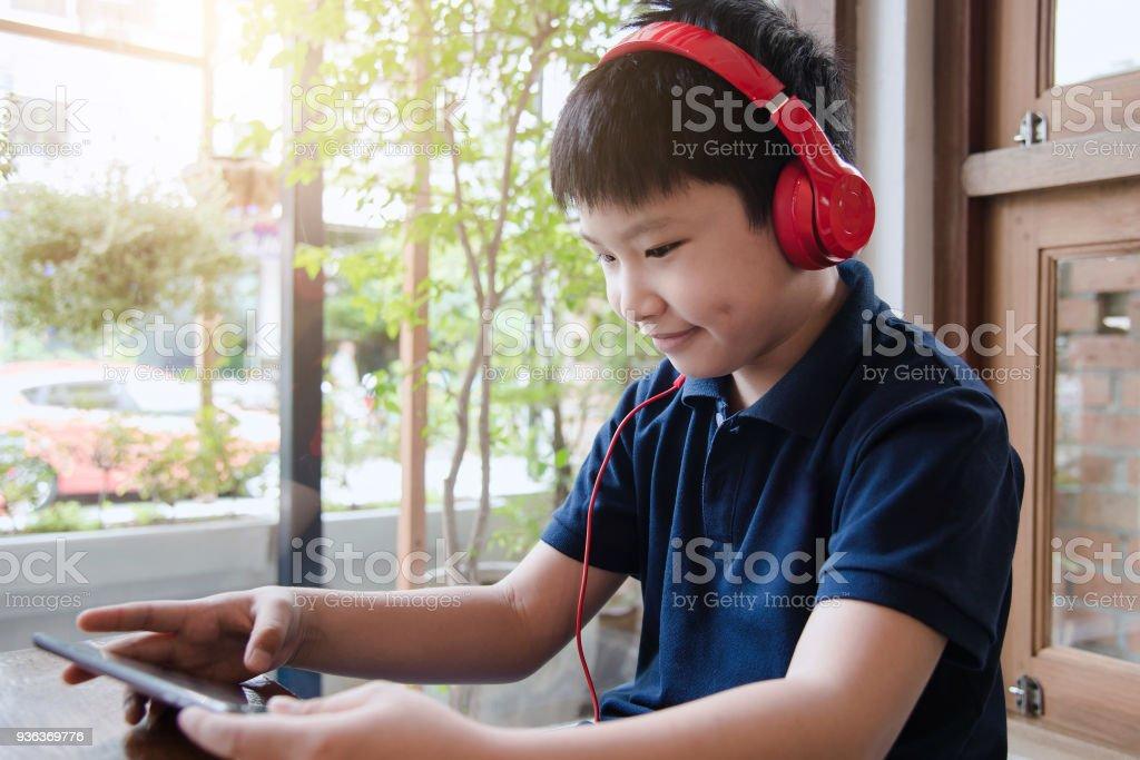 Escuchar música atractivo asiatico por auriculares en el cuarto. - foto de stock