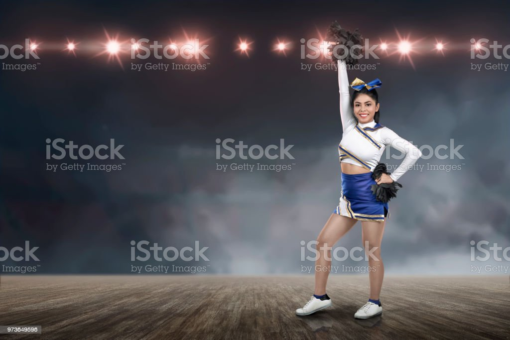 Attractive asian cheerleader holding pom-poms stock photo