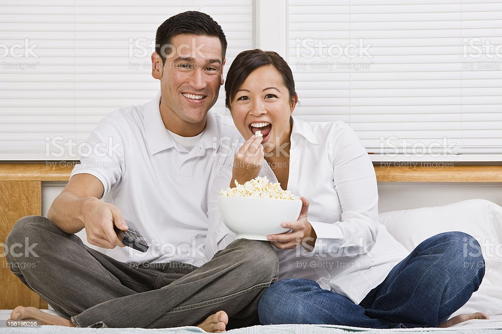 Attractive Asian Couple Eating Popcorn in Bed royalty-free stock photo