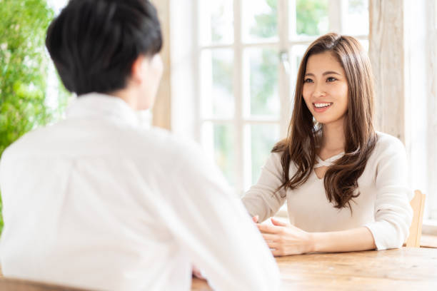 attractive asian couple talking in living room - asia orientale foto e immagini stock
