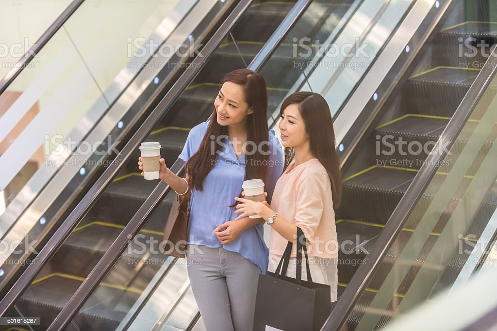 Attractive Asian Girls Riding Escalator in Mall stock photo