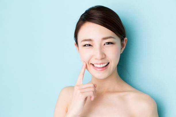 imagen de la belleza de la mujer asiática atractiva aislado sobre fondo azul - asian woman fotografías e imágenes de stock
