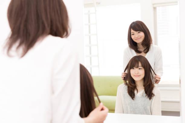 鏡の前で魅力的なアジア女性 - 美容院 ストックフォトと画像