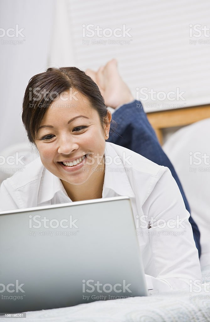 Attractive Asian Woman Lying Down with Laptop royalty-free stock photo