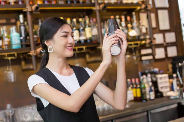 Attraktive Asiatin Mixgetränk für Kunden am Schalter Bar, Frau bereitet ein Cocktail Shaker. Frau mit Barkeeper Konzept. – Foto