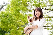 犬と公園でリラックスできる魅力的なアジア女性