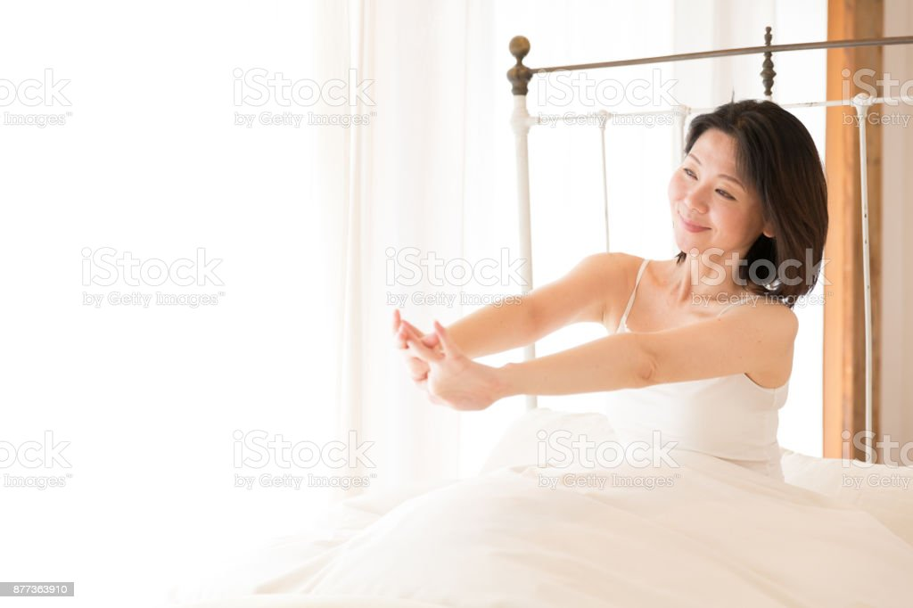 attractive asian woman relaxing on bed stock photo
