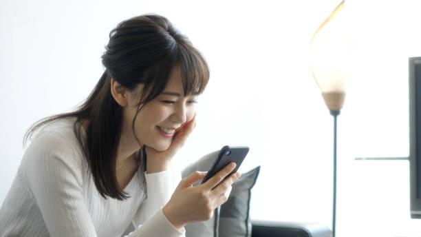 リビングルームでスマートフォンを使用して、魅力的なアジアの女性。 - 女性 ストックフォトと画像