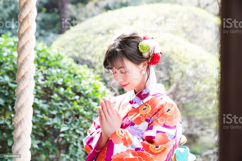 Attractive asian woman wearing japanese kimono praying at a Shinto shrine. stock photo